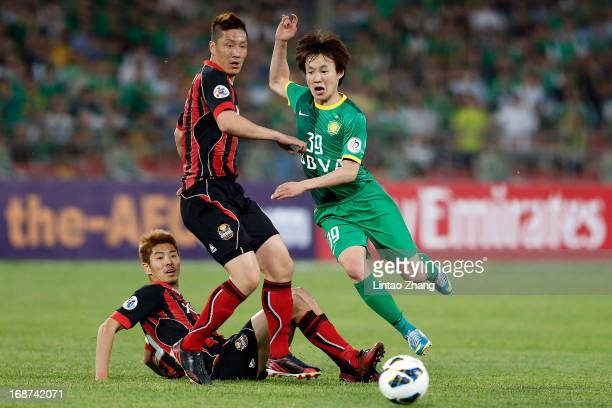 Piao Cheng of Beijing Guoan challenges Kim JinKyu of Seoul FC during the AFC Champions League Round of 16 match between Beijing Guoan and Seoul FC at...