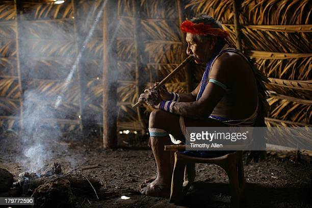Piaora tribesman plays bamboo flute in hut