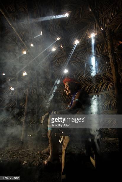 Piaora tribesman sits in smoke filled hut