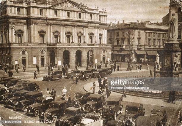 Piazza and Teatro alla Scala. Taxi station in front of the building, and parking next to the monument to Leonardo. Postcard, photocollograph, Italy,...