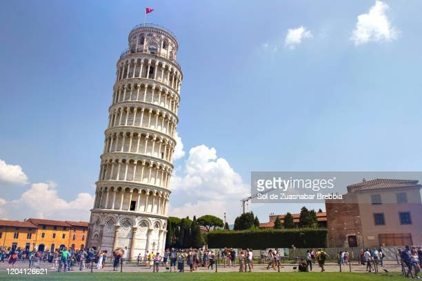 piazza dei miracoli with the leaning tower of pisa surrounded by tourists on a bright sunny day - pisa stock pictures, royalty-free photos & images