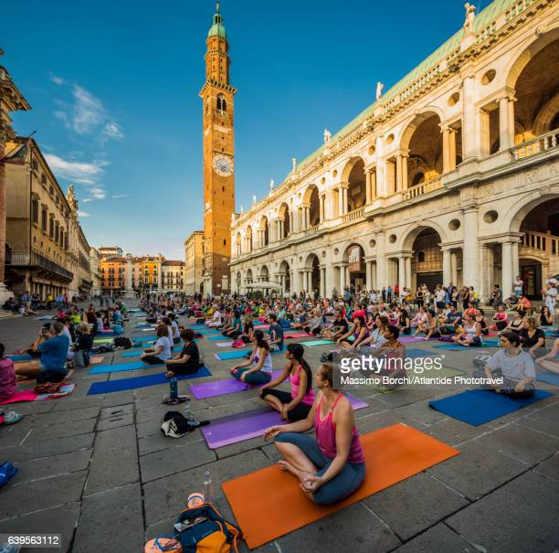 Piazza (square) dei Signori, yoga lesson, the Basilica Palladiana (Palladio architect) on the right and the Torre (tower) Bissara on the background