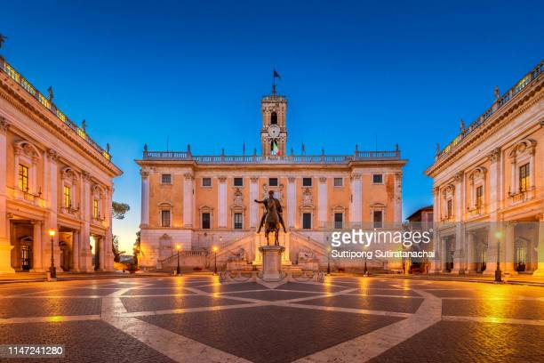 piazza del campidoglio on the top of capitoline hill with the facade of palazzo senatorio and the replica of equestrian statue of marcus aurelius in rome, italy - courtyard stock pictures, royalty-free photos & images