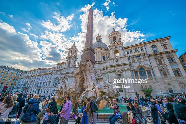 Piazza Navona with crowd of people and a water fountain and sunshine in Rome, Italy.