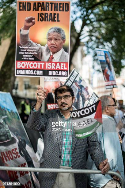 Pic shows a a man holding a banner with Nelson Mandela in the propalestina demonstration Hundreds of antiIsrael protesters marched through the...