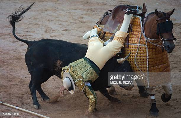 TOPSHOT A picador falls from his horse as a Victoriano del Rio Cortes' charges during the sixth corrida of the San Fermin Festival in Pamplona on...
