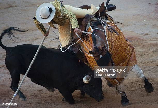 A picador falls from his horse as a Victoriano del Rio Cortes' charges during the sixth corrida of the San Fermin Festival in Pamplona on July 12...