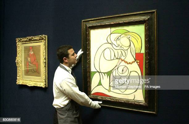 Picasso's oil on canvas workNu au collier being hung by a Christie's employee * The painting is one Pablo Picasso's works to be sold at Christie's...