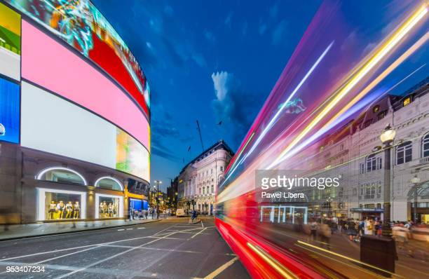piccadilly circus in london with a light trails left by a passing double-decker bus at night. - piccadilly circus imagens e fotografias de stock