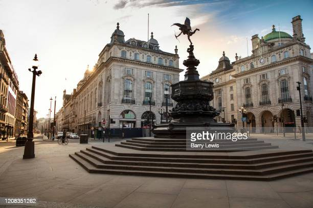 Piccadilly Circus is deserted at evening rush hour during the Coronavirus pandemic on 26th March 2020 in London United Kingdom The government...