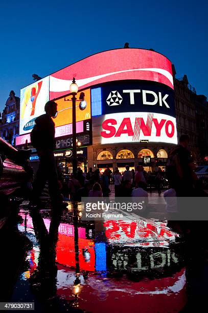 Piccadilly Circus neon billboards reflecting on the wet surface at night. Coka Cola, Samsung, TDK, Sanyo, McDonalds ads on top of the GAP building.