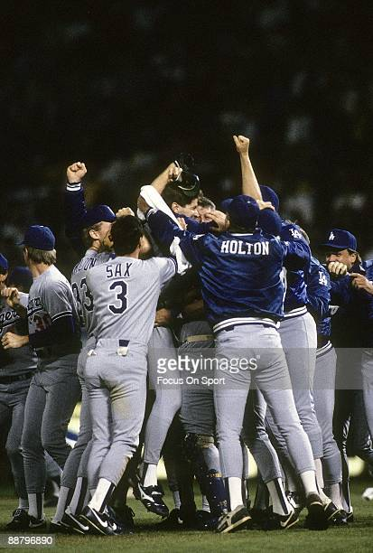 Picher Orel Hershiser of the Los Angeles Dodgers is mobbed by teammates Steve Sax and Brian Holton and others with jubilation after Hershiser pitched...
