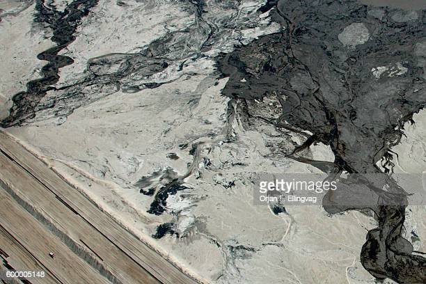 A pick up truck passes a tailings pond at the Syncrude open pit oil excavation mine in Fort McMurray The tailings ponds are areas of refused mining...