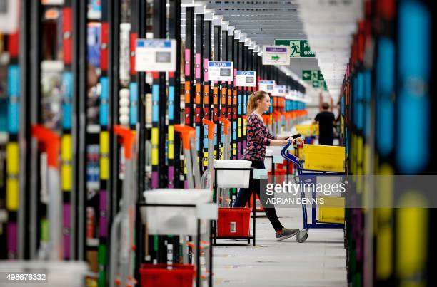 A 'picker' worker collects items from storage shelves as she collates a customer order inside an Amazoncouk fulfillment centre in Hemel Hempstead...