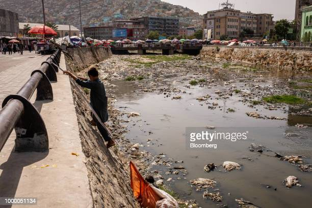 Pickers climb a riverbank with sacks of recyclable materials collected from the Kabul River in Kabul Afghanistan on Thursday July 12 2018 US...