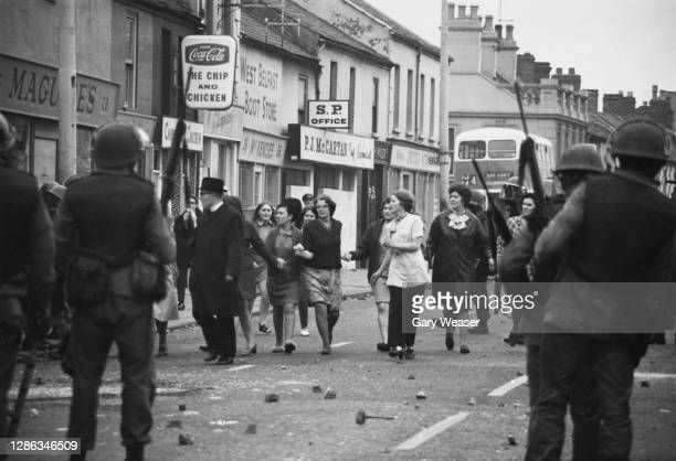 Picket of women who tried to end the violence pass through the lines of British troops to safety during riots in the Falls Road area of Belfast,...
