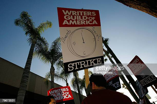 A picket sign addresses the question of whether the strike may end soon while Writers Guild of America members and supporters picket in front of NBC...