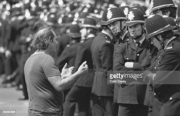 A picket talking to policemen during a demonstration by striking miners