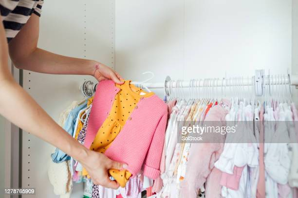 picking daughter's outfit - baby clothing stock pictures, royalty-free photos & images