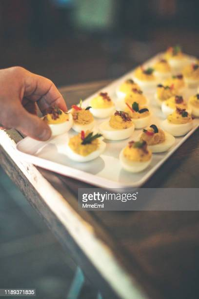 picking deviled egg - mmeemil stock photos and pictures