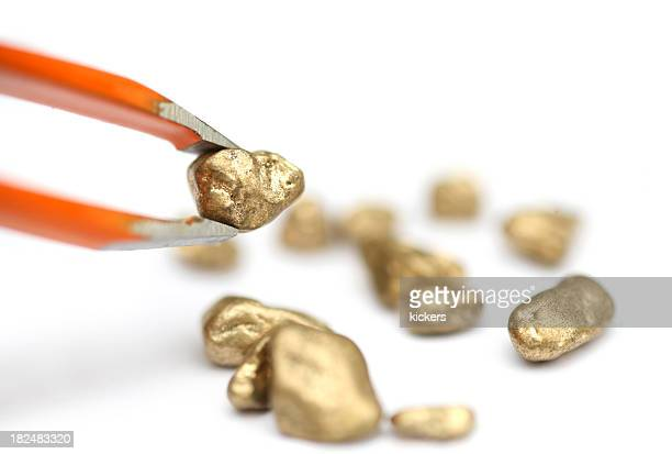 Picking gold with tweezer, isolated