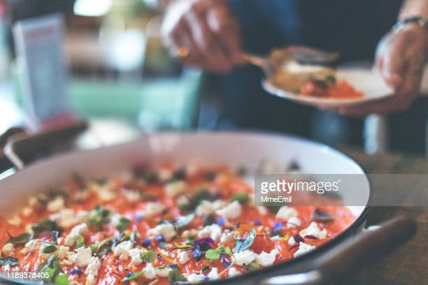 picking in large plate of gravlax to share - mmeemil stock photos and pictures