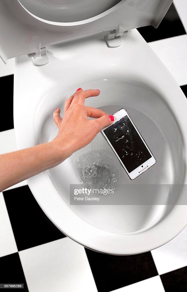 Picking smart phone out of toilet : Stock Photo