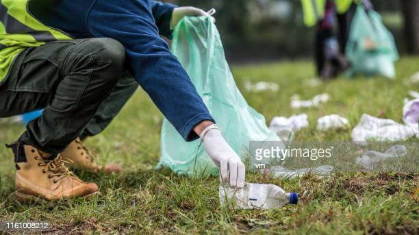 picking up a plastic bottle during park clean-up - picking up stock pictures, royalty-free photos & images