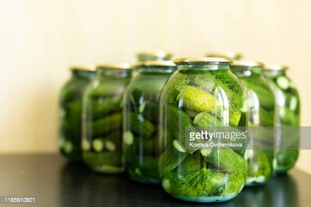 pickled cucumbers in glass jar on a gray wooden table. - pickled stock pictures, royalty-free photos & images