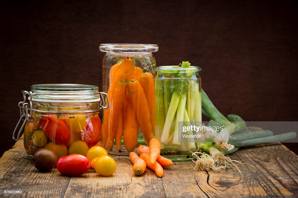 Pickled spring onions and fermented carrots in glasses : Stock Photo