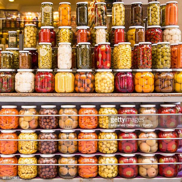 pickles in glass jars arranged on shelves at market for sale - neat stock pictures, royalty-free photos & images