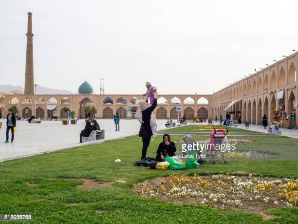 Picknickers relaxing at Maydane Imam Square also known as Naqshe Jahan Square in Esfahan Iran It is a UNESCO World Heritage Site
