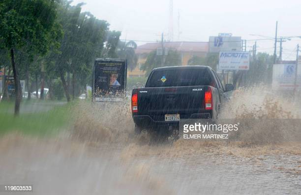 A pickup drives along a flooded street during heavy rain in Managua Nicaragua on July 22 2011 Leaders of the Central American countries and...