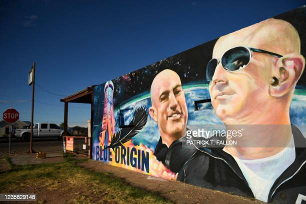 Pickup truck drives past a mural of billionaire Amazon founder Jeff Bezos and his brother Mark Bezos with a Blue Origin rocket in Van Horn, Texas on...
