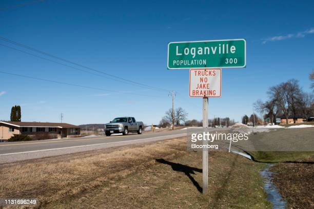 A pickup truck drives past a town sign in Loganville Wisconsin US on Saturday March 16 2019 The worst agriculturaldownturnsince the 1980s is taking...