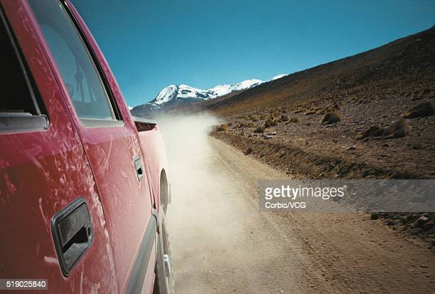 Pickup Truck Driving Down Dirt Road