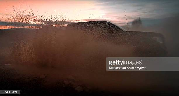 Pick-Up Truck Driving Through Mud Puddle During Sunset