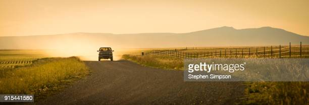 pick-up truck in the distance on dusty dirt road in afternoon light