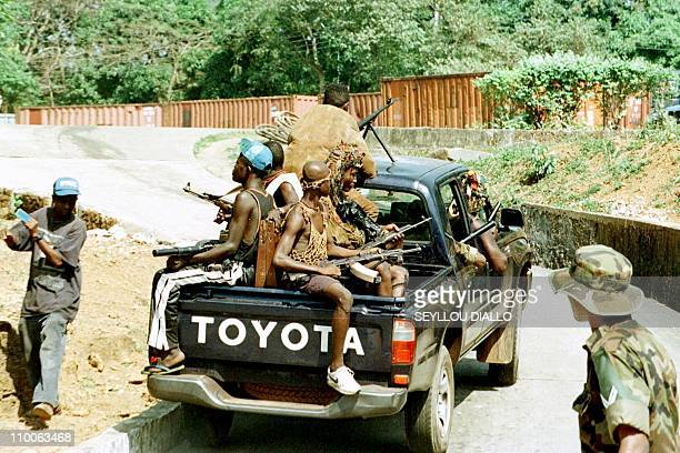 Pickup truck loaded with Camajors militiamen passes a Freetown civilian and an ECOMOG soldier on a road of the Sierra Leone capital 21 January....