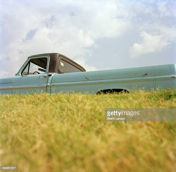 a pick-up truck next to a field - gras stock pictures, royalty-free photos & images