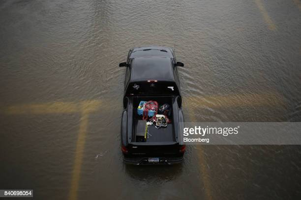 A pickup truck sits abandoned in floodwaters from Hurricane Harvey in Dickinson Texas US on Tuesday Aug 29 2017 Estimates for damages caused by...