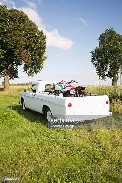 A pickup truck with motorbikes in a field