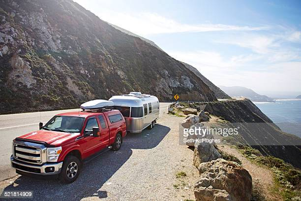 Pick-up truck with trailer attached on mountain road, Big Sur, California, USA
