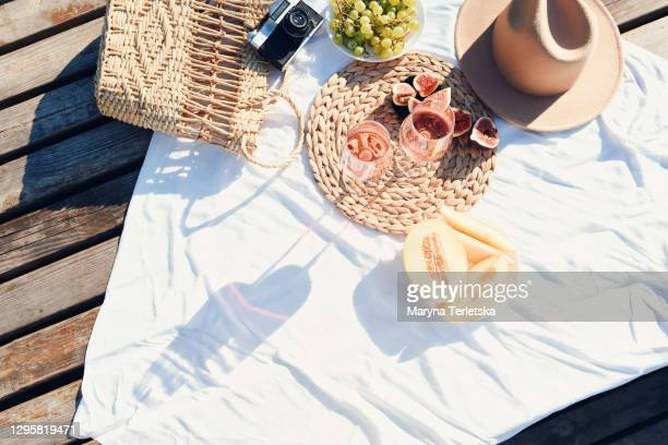 picnic at the pier near the water. - picnic blanket stock pictures, royalty-free photos & images