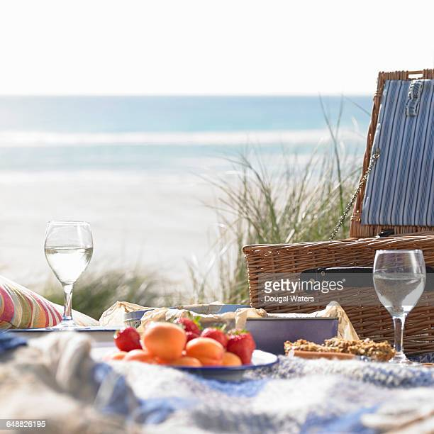 Picnic basket at beach with fruit and wine glasses