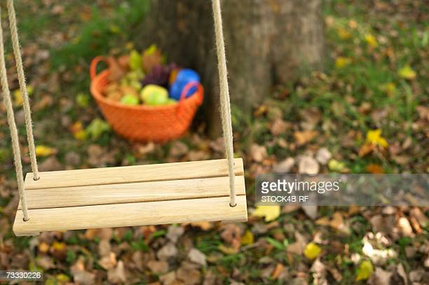 Picnic basket behind a wooden swing in front of a deciduous tree, close-up, selective focus