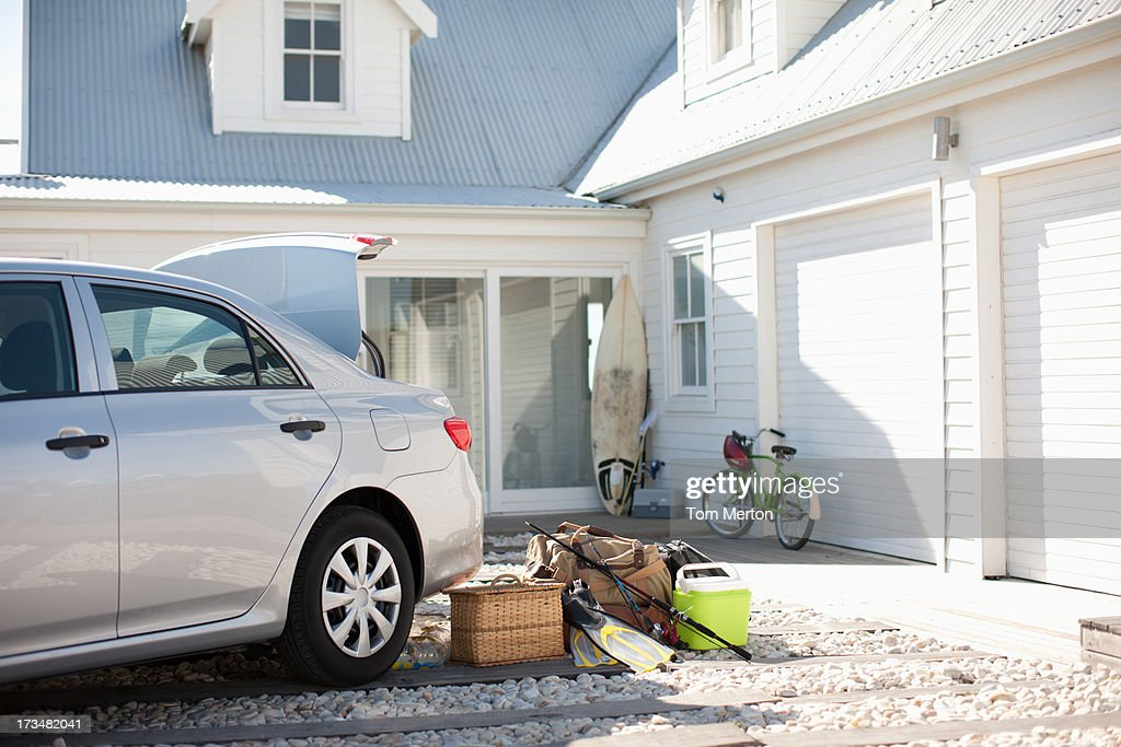 Picnic basket, fishing rod, flippers and bags outside car in driveway : Stock Photo