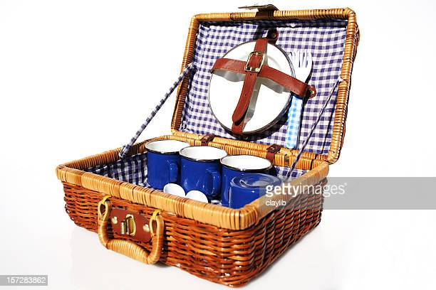 A picnic basket made of wicker and blue dishes