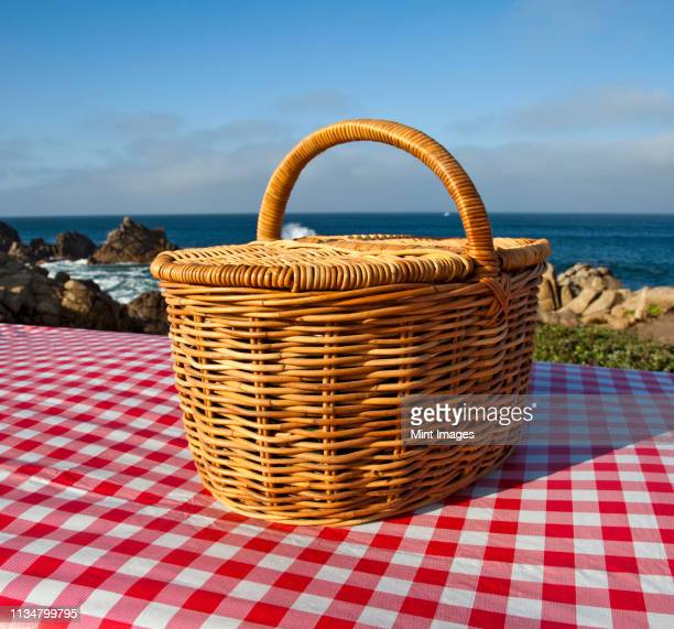 picnic basket on wooden picnic table - hamper stock pictures, royalty-free photos & images