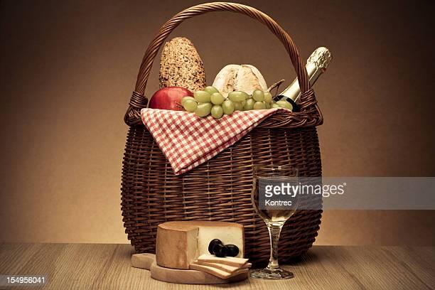 Panier de pique-nique avec un pain, vin, du fromage, des olives et des pommes